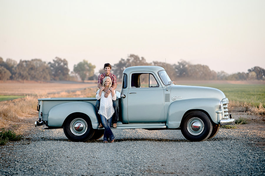A couple sitting on an old powder blue classic truck