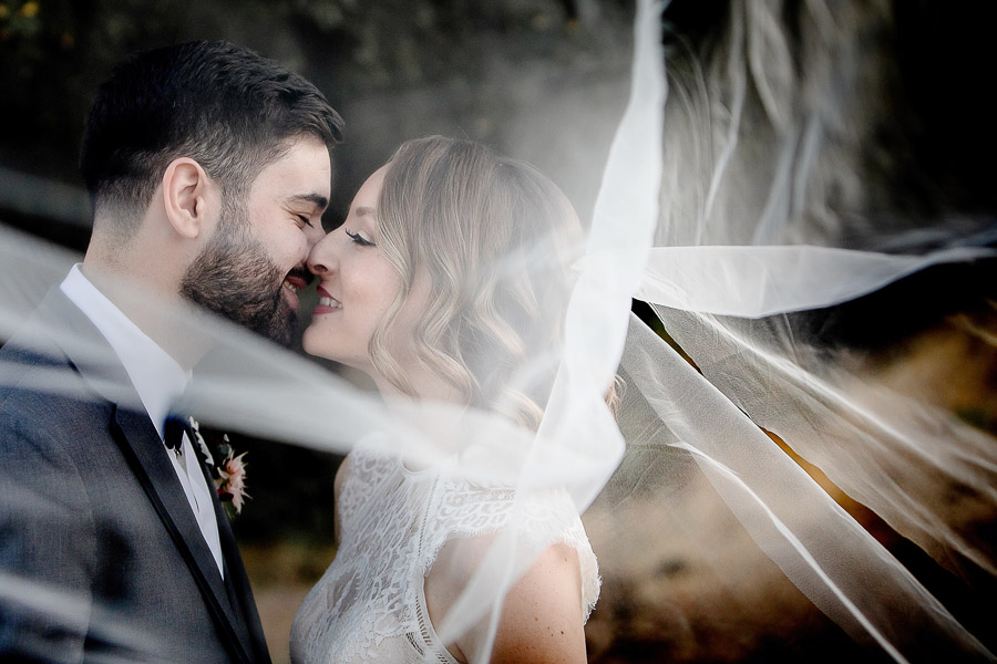 bride and groom kissing under a long veil