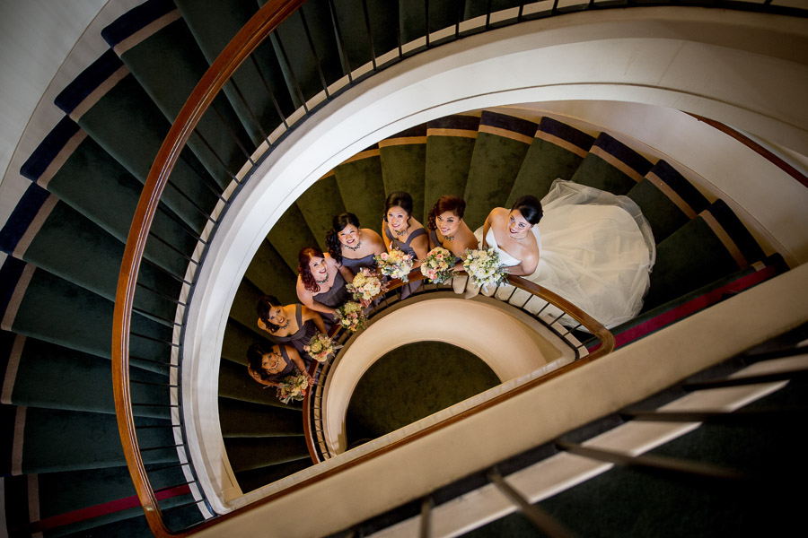 bridal party on spiral staircase in an old library downtown