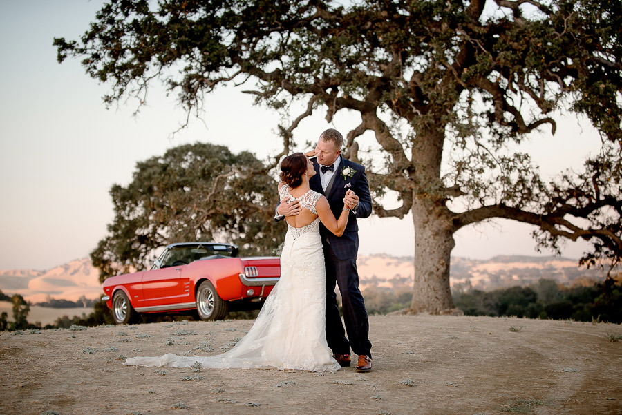 bride and groom dancing with a classic red car at sunset