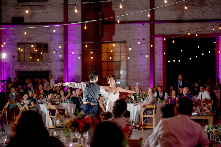 bride and groom having their first dance in a lit up purple reception
