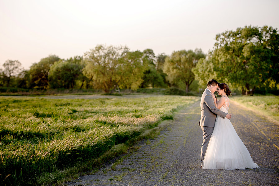 the bride and groom in a grassy field with gravel road during sunset