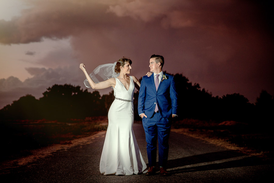 bride and groom with killer purple sunset